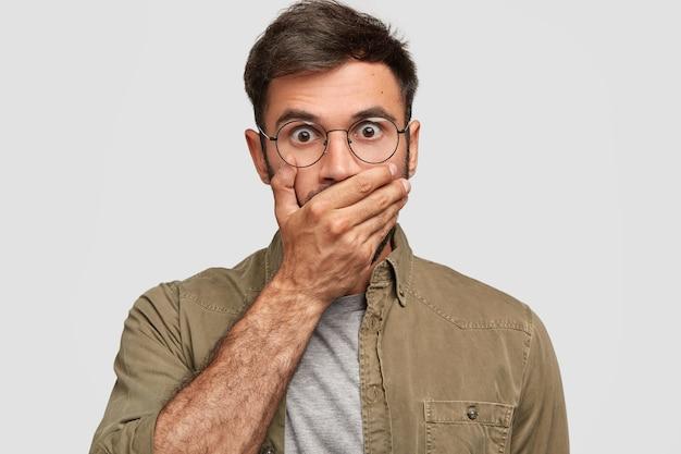 ひどい!驚いた表情で唖然としたバグのある目の男性は、手のひらで口を覆い、重要な情報を秘密にし、黒髪で、カジュアルなシャツを着て、屋内でポーズをとります。人と反応