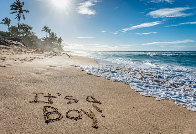 It's a boy, gender reveal written in the sand on sunset beach in hawaii