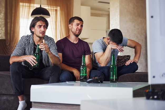 It's a defeat. sad three friends watching soccer on tv at home together.