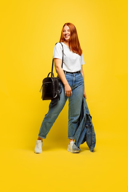 It's easier to be follower. need minimum clothes to go. caucasian woman's portrait on yellow background. beautiful female red hair model. concept of human emotions, facial expression, sales, ad.