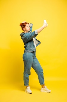 It's easier to be follower. need minimum clothes for selfie. caucasian woman's portrait on yellow background. beautiful female red hair model. concept of human emotions, facial expression, sales, ad.