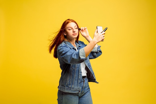 It's easier to be follower. need no selfie for make up. caucasian woman's portrait on yellow background. beautiful female red hair model. concept of human emotions, facial expression, sales, ad.