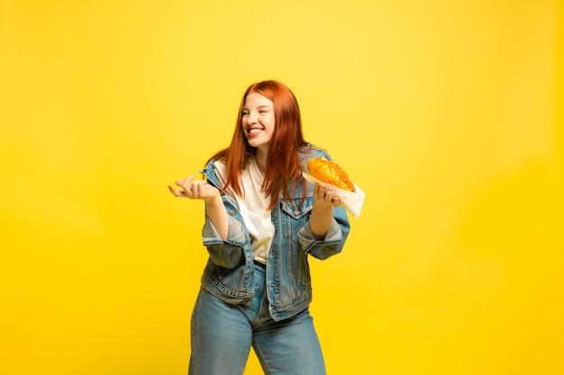 È più facile essere follower. non è necessario scattare foto con il cibo. la donna caucasica è su sfondo giallo. bello modello femminile dei capelli rossi. concetto di emozioni umane, espressione facciale, vendite, annuncio.
