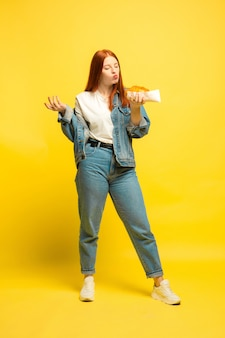 It's easier to be follower. don't need to take photo with food. caucasian woman's on yellow background. beautiful female red hair model. concept of human emotions, facial expression, sales, ad.
