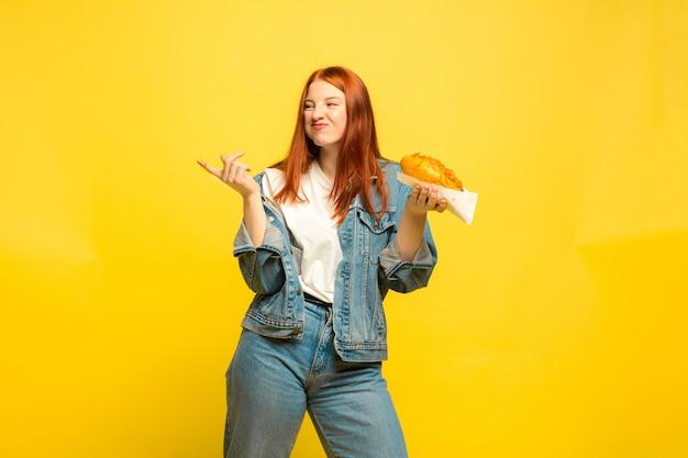 フォロワーになるのは簡単です。食べ物で写真を撮る必要はありません。白人女性は黄色の背景に。美しい女性の赤い髪のモデル。人間の感情、表情、販売、広告の概念。