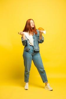 フォロワーになるのは簡単です。食べ物と一緒に写真を撮る必要はありません。黄色の背景に白人女性。美しい女性の赤い髪のモデル。人間の感情、表情、販売、広告の概念。