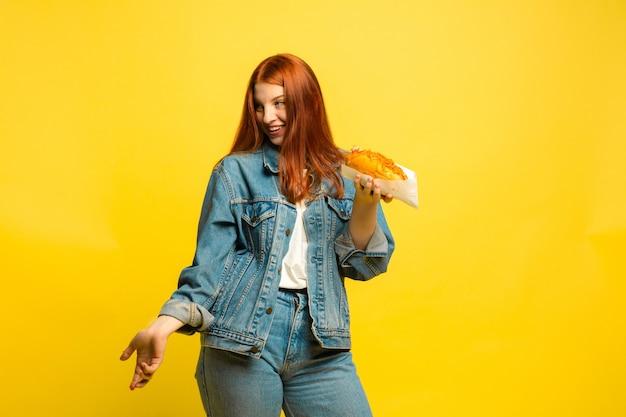 Легче быть последователем. не нужно фотографировать с едой. кавказская женщина на желтом фоне. модель красивых женских красных волос. понятие человеческих эмоций, выражения лица, продаж, рекламы.