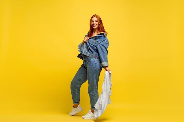 フォロワーになるのは簡単です。シャツが1枚の場合は、洗濯が速くなります。黄色の背景に白人の女性の肖像画。美しい赤い髪のモデル。人間の感情、表情、販売、広告の概念。