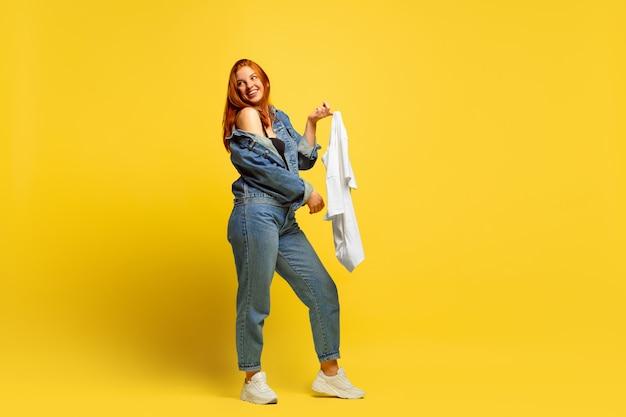 フォロワーになるのは簡単です。シャツが1枚だけの場合は、洗濯が速くなります。黄色の背景に白人女性の肖像画。美しい赤い髪のモデル。人間の感情、表情、販売、広告の概念。