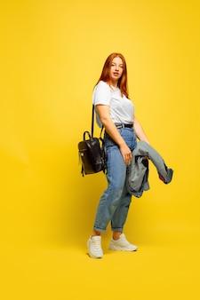 추종자가되는 것이 더 쉽습니다. 갈 최소한의 옷이 필요합니다. 노란색 바탕에 백인 여자의 초상화입니다. 아름다운 여성의 빨간 머리 모델. 인간의 감정, 표정, 판매, 광고의 개념.