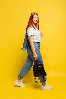 フォロワーになるのは簡単です。行くには最小限の服が必要です。黄色の背景に白人女性の肖像画。美しい女性の赤い髪のモデル。人間の感情、顔の表情、販売、広告の概念。