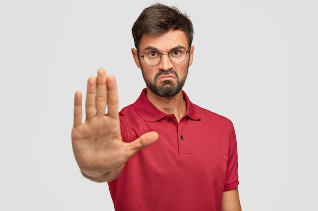 禁じられています!怒っている不機嫌な若い男性は顔をしかめ、停止ジェスチャーを示し、手のひらを前に保ち、ひどく不快なことから自分自身を防ごうとし、白で隔離されたカジュアルなtシャツを着ています