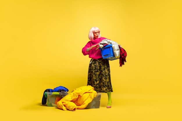 It's hard to be influencer. longer laundry with collection of clothes. caucasian woman's portrait on yellow background. beautiful blonde model. concept of human emotions, facial expression, sales, ad.