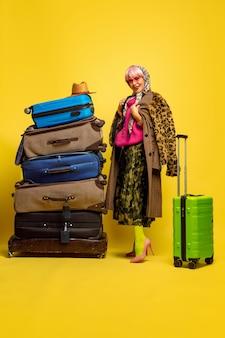 Трудно быть влиятельным лицом. много одежды для путешествий. портрет кавказской женщины на желтом фоне. красивая блондинка модель. концепция человеческих эмоций, выражения лица, продаж, рекламы.
