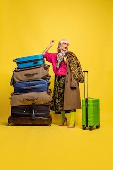 インフルエンサーになるのは難しいです。旅行に行く服がたくさん。黄色の背景に白人女性の肖像画。美しい金髪モデル。人間の感情、表情、販売、広告の概念。