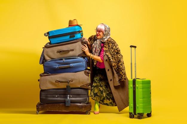 インフルエンサーになるのは難しいです。旅行に行く服がたくさん。黄色の背景に白人女性の肖像画。美しい金髪モデル。人間の感情、顔の表情、販売、広告の概念。