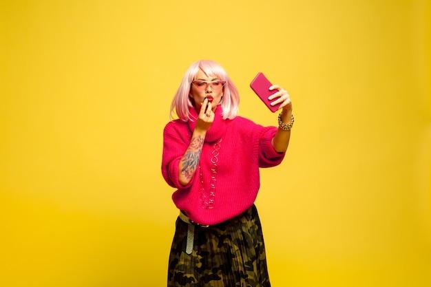 Трудно быть влиятельным лицом. не могу накраситься без селфи или видеоблога. портрет кавказской женщины на желтом фоне. красивая блондинка модель. концепция человеческих эмоций, выражения лица, продаж, рекламы.
