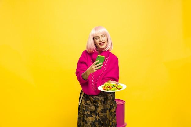 Трудно быть влиятельным лицом. сначала селфи, потом поела. нужно заранее приготовить блюдо. портрет кавказской женщины на желтом. красивая блондинка модель. концепция человеческих эмоций, выражения лица, продаж, рекламы.