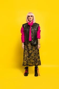 インフルエンサーになるのは難しいです。明るい服装でスタイリッシュに。黄色の背景に白人女性の肖像画。美しい金髪モデル。人間の感情、表情、販売、広告の概念。