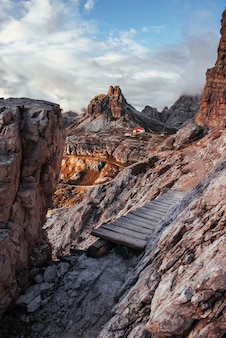 It's a long way. extreme path at the edge of the hills with wooden little bridge to the way to building standing at dolomites mountains.