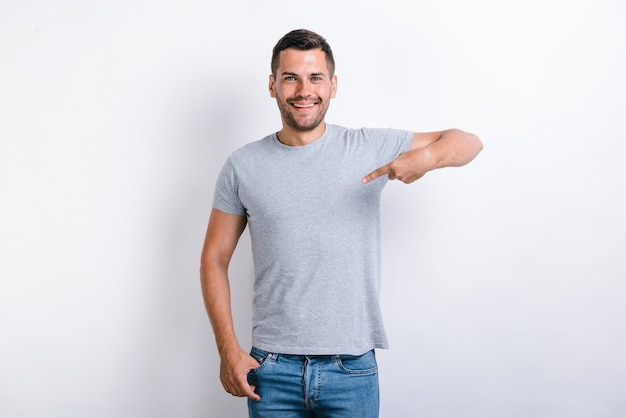It's me! ambitious young man with toothy smile on face pointing with finger on himself, confident teenager. indoor studio shot isolated on white background
