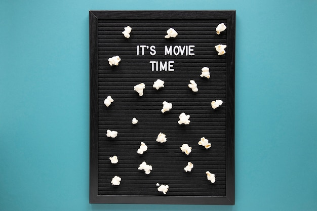 It's movie time lettering on black board with popcorn
