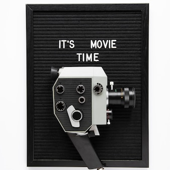 It's movie time lettering above vintage movie camera