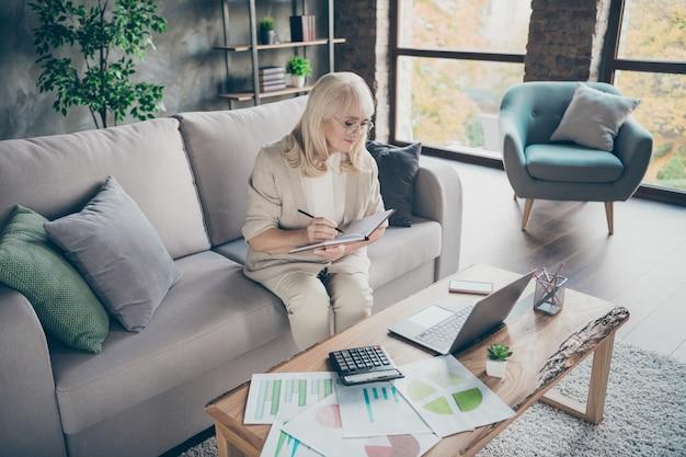 공부하기에 늦지 않았습니다! 노트북을 들고 메모장을 사용하여 흰 머리 세 할머니의 사진 온라인 마스터 클래스 비즈니스 강의 수업 앉아 소파 디반 룸 사무실 실내