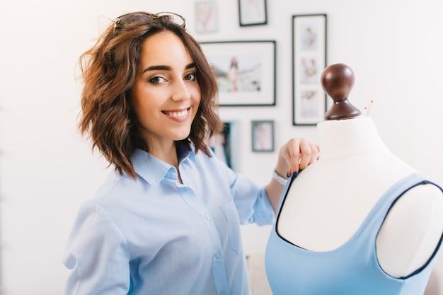 È un ritratto di una ragazza nello studio del laboratorio. ragazza castana con una camicia blu sta creando un vestito blu sul manichino. sta sorridendo alla telecamera.