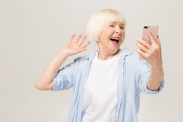 Пришло время селфи! изображение жизнерадостной зрелой старухи, стоящей изолированной над белой второстепенной стеной, говорящей по мобильному телефону.