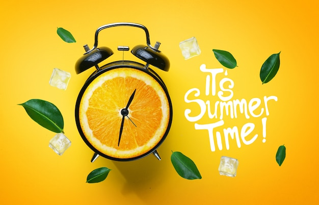 It's summer time typography. alarm clock of orange fruit green leaves and ice cube flying