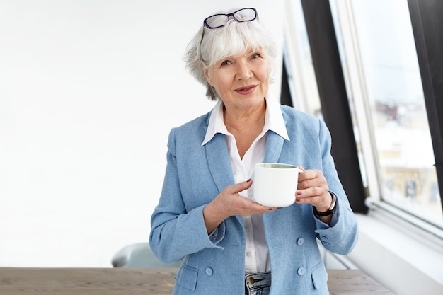 It's time for coffee break. indoor image of elegant middle aged businesswoman wearing fashionable clothes and glasses holding white cup while drinking tea at her office, standing by window and smiling