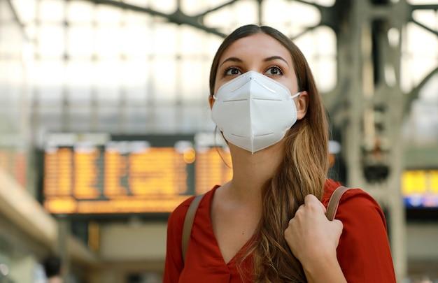 旅行に戻りましょう。駅でkn95 ffp2フェイスマスクを着ている旅行者の女の子のクローズアップ