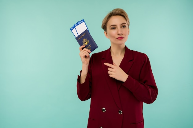 It's time to travel. a modern trendy smiling woman in red suit pointing at air tickets and a passport in her hand.