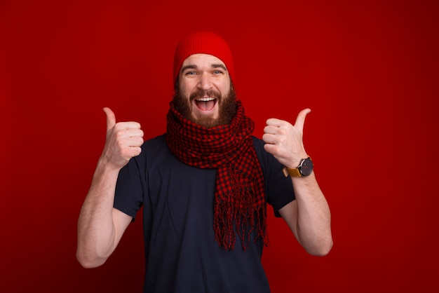 It's time for warm clothes, bearded guy wearing hat and scarf, showing thumbs up over red space