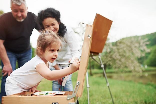 Будет круто смотреться. бабушка и дедушка веселятся на природе с внучкой. концепция живописи