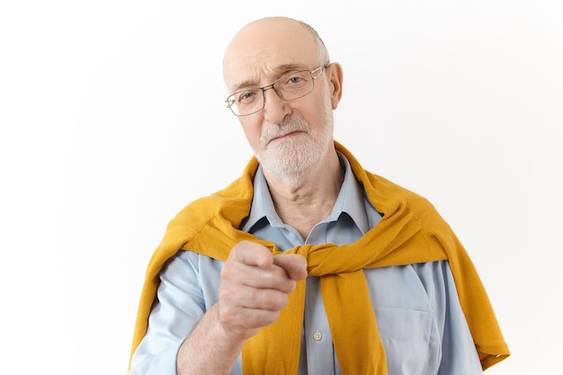 それはあなたの責任です。エレガントなフォーマルウェアと眼鏡で人差し指をカメラに向け、警告ジェスチャーをしたり、誰かを悪い間違いで非難したりする、怒っている厳格な年配のボスの水平方向のショット