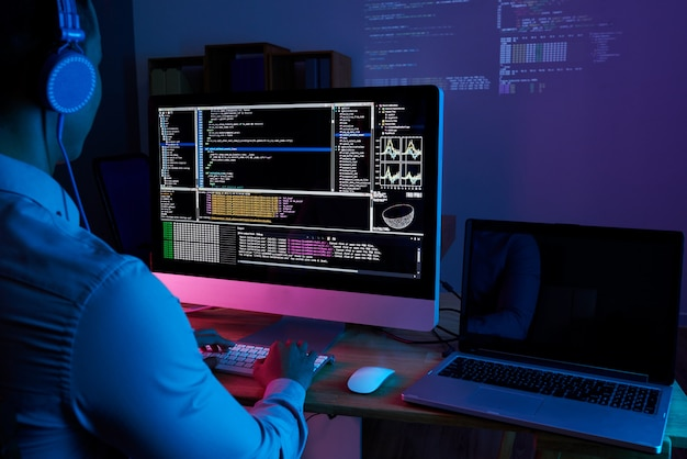 It specialist checking code at computer in the dark office at night