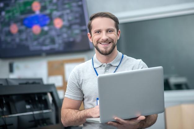 It специалист. симпатичный улыбающийся молодой бородатый человек, стоящий с открытым ноутбуком во время работы в помещении