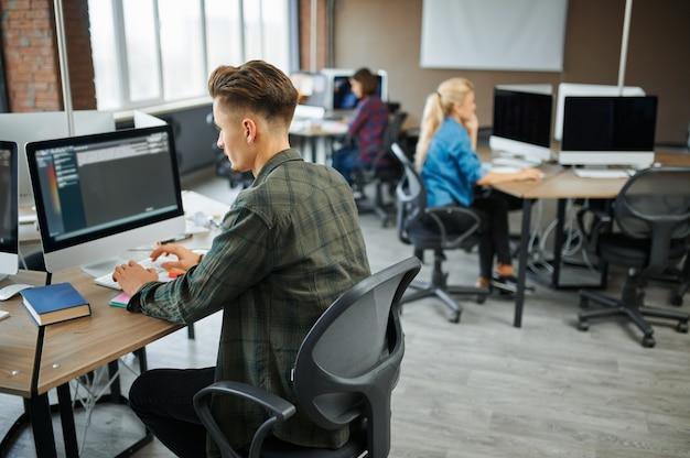 Группа ит-специалистов работает за столами в офисе. веб-программист или дизайнер на рабочем месте, творческое занятие. современные информационные технологии, корпоративный коллектив