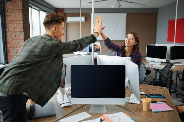 Ит-специалисты приветствуют друг друга в офисе. веб-программист или дизайнер на рабочем месте, творческое занятие. современные информационные технологии, корпоративный коллектив