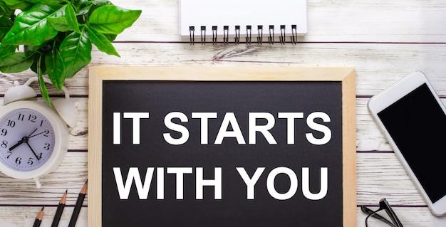 鉛筆、スマートフォン、白いメモ帳、鉢植えの緑の植物の近くの黒い背景に書かれたあなたから始まります