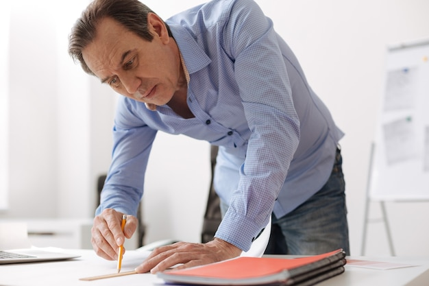 Do it in such a way. professional serious senior engineer drawing a blueprint and stnding near table in the office
