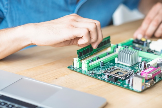 It technician repairing hardware equipment's on wooden table
