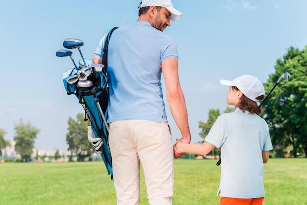 素晴らしいゲームでした!若い男と彼の息子がゴルフコースを歩きながら手をつないでお互いを見ている背面図