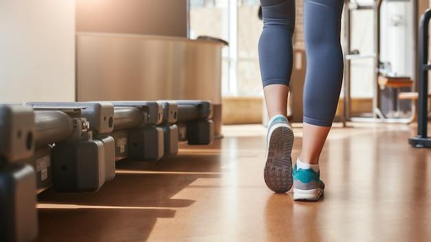 Это была отличная тренировка, вид сзади ног женщины в леггинсах и ходьбе синих кроссовок.
