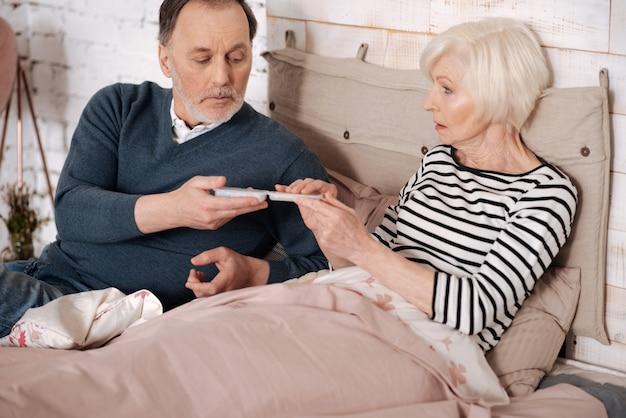 Это поможет. старший красавец дает коробку с таблетками своей пожилой больной жене, лежащей на кровати, накрытой теплым одеялом.