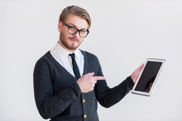 Это облегчит тебе жизнь. красивый молодой человек в очках, держащий цифровой планшет и указывая на него, стоя на сером фоне