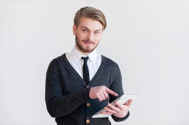 Это облегчит тебе жизнь. красивый молодой человек в очках держит цифровой планшет и улыбается, стоя на сером фоне