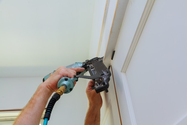 Do it yourself home owner repairing door frame molding with nail gun,